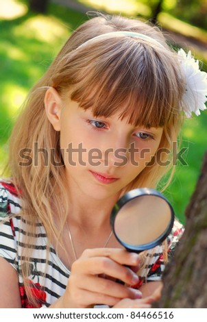 portrait of beautiful blond girl looking through magnifying glass  in the park - stock photo