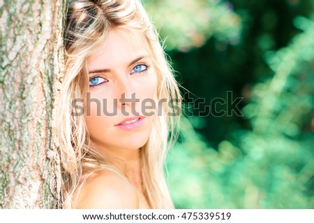 Portrait of beautiful blond girl with blue eyes intense look in the resting nature in a plant