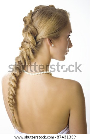 Portrait of beautiful blond girl with creative braid hairdo and pearls