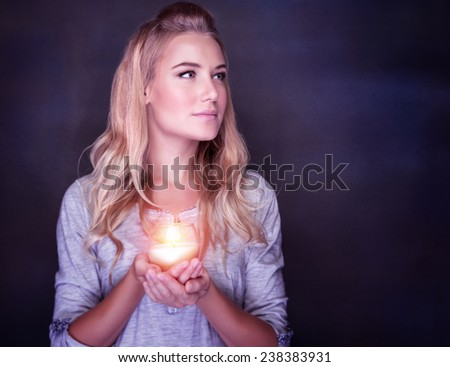 Portrait of beautiful blond girl with glowing candle in hands on dark background, praying on Christmas time, traditional Christian holiday - stock photo