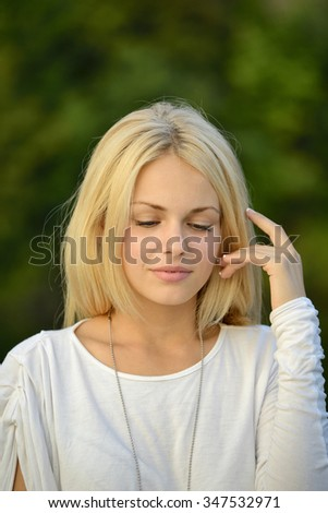 Portrait of beautiful blond girl with green background
