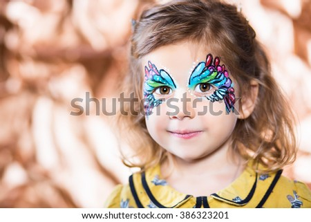 Portrait of beautiful blond girl with painted face - stock photo