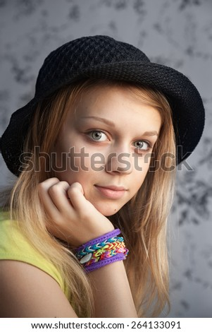 Portrait of beautiful blond teenage girl in black hat and rubber loom bracelets, vintage toned photo filter, instagram style effect - stock photo