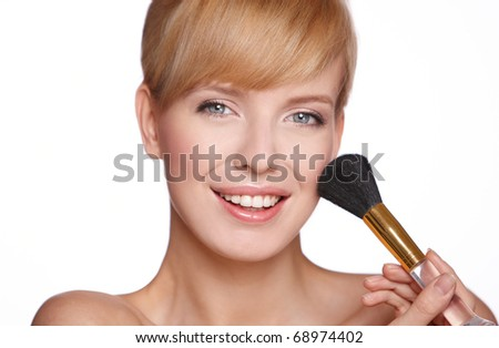 Portrait of beautiful blond  woman applying cosmetic isolated on beige - stock photo