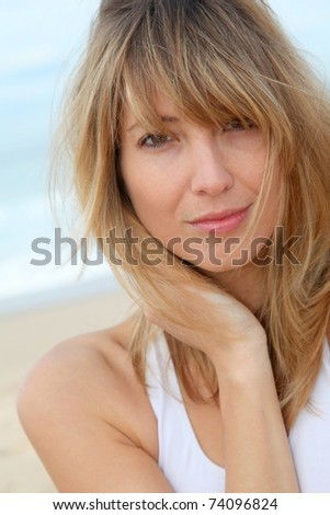 Portrait of beautiful blond woman at the beach - stock photo