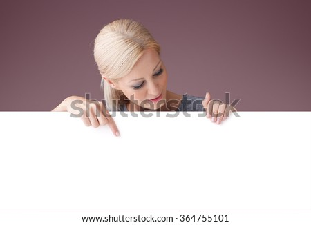 Portrait of beautiful blond woman holding in her hands a white billboard while showing something in her finger and looking down.