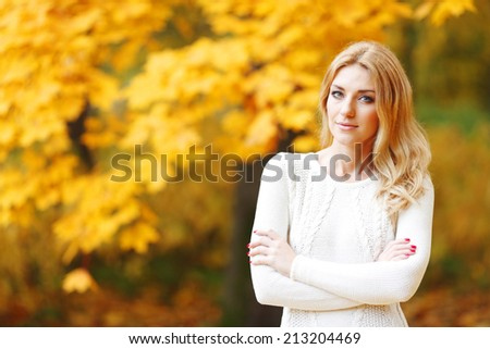 Portrait of beautiful blond woman in autumn park - stock photo