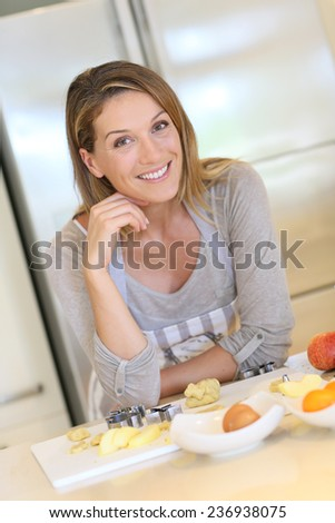 Portrait of beautiful blond woman in modern kitchen - stock photo
