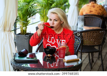Portrait of beautiful blond woman sitting at outdoors cafe