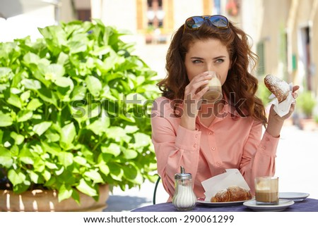 Portrait of beautiful blond woman sitting in outdoors cafe in Italy, drinking coffee and eating croissant. - stock photo