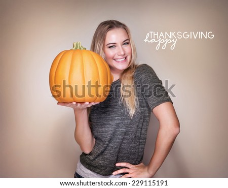 Portrait of beautiful blond woman with big orange pumpkin in hands isolated on beige background, happy Thanksgiving day  - stock photo
