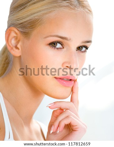 Portrait of beautiful blond woman with finger on lips - stock photo