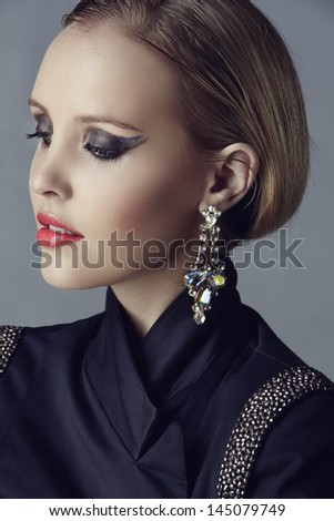 Portrait of beautiful blond woman with studio pulled back wearing diamante statement earrings and blazer with beads on studio background - stock photo