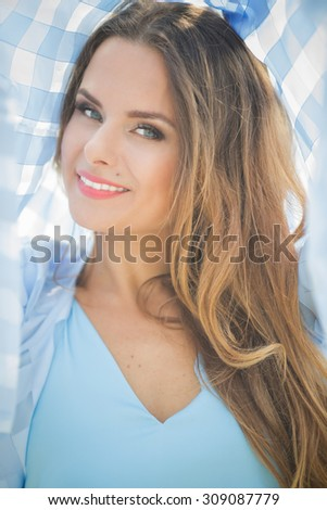 Portrait of beautiful blond young woman' shot outdoors. Smiling lady in blue shirt posing for photographer in the city.