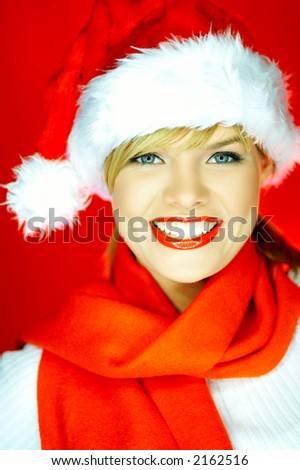 Portrait of beautiful blond young woman wearing santa claus hat on red background