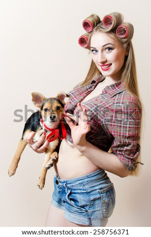 Portrait of beautiful blond young woman with curlers on her head and a dog in her arms - stock photo