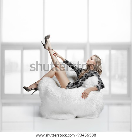 portrait of beautiful blonde blue-eyed girl sitting in big furry arm-chair - stock photo