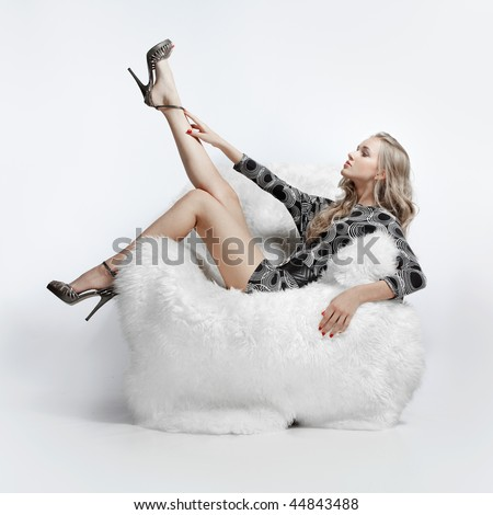 portrait of beautiful blonde blue-eyed girl sitting in big furry armchair - stock photo