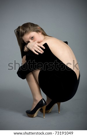 Portrait of beautiful blonde caucasian girl lying down. Showing backside. - stock photo