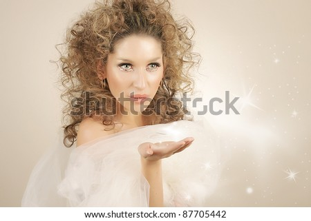 portrait of beautiful blonde  girl blowing snow flakes from hands - stock photo