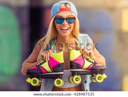 Portrait of beautiful blonde girl in cap and glasses looking at camera and smiling while standing with her rollers in skate park - stock photo