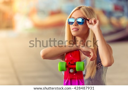 Portrait of beautiful blonde girl in glasses looking away while leaning on her skateboard - stock photo