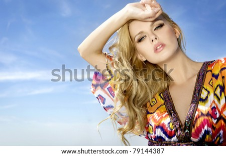 portrait of beautiful blonde girl in sunglasses on background blue sky - stock photo