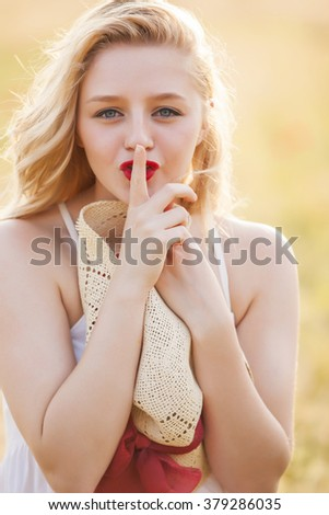 Portrait of beautiful blonde girl in white dress with straw hat with finger on lips expressing shh gesture, quiet, silence. - stock photo