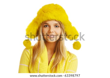 portrait of beautiful blonde girl in yellow furry cap with ear flaps - stock photo