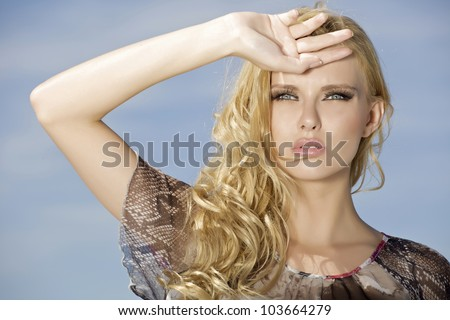 portrait of beautiful blonde girl on background blue sky - stock photo