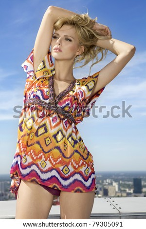 portrait of beautiful blonde girl on background blue sky - stock photo