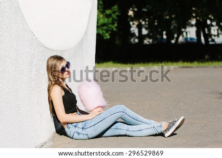 portrait of beautiful blonde girl sitting outside with pink cotton candy. Wearing sunglasses with stars. Red lips. White background, not isolated. Looking sad - stock photo