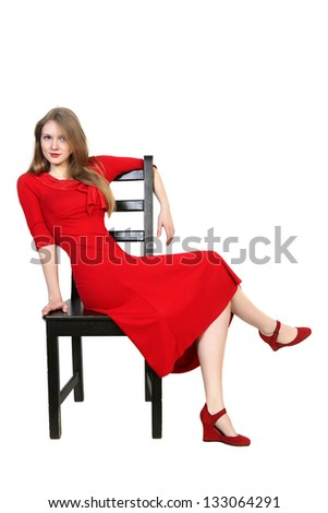 Portrait of  beautiful blonde in red dress sitting on a chair. Isolated on white background - stock photo
