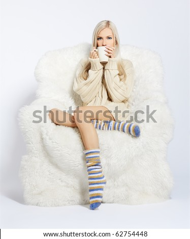 portrait of beautiful blonde sitting with cup on big white furry arm-chair - stock photo
