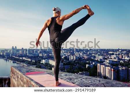 Portrait of beautiful blonde strong woman in sportwear doing workout stretching on the roof of a skyscraper above the big city at early morning. Female sporty muscular body. Sunrise sunny light.  - stock photo