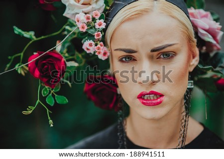 Portrait of beautiful blonde with a roses on her head