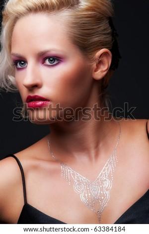 portrait of beautiful blonde with hairdo over dark background - stock photo