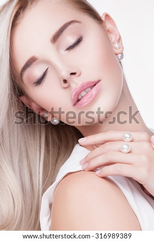 Portrait of beautiful blonde woman.beauty.An attractive woman with a healthy skin.Light make-up.Jewelry beautiful young blond woman. White clothes isolated on a white background. Lady with eyes closed - stock photo