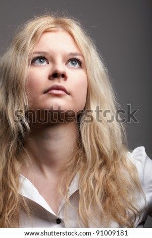portrait of beautiful blonde woman grey background