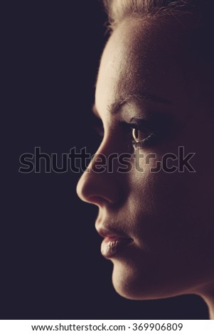 Portrait of beautiful blonde woman in darkness with soft light on her face, pensive silhouette in on black background. - stock photo