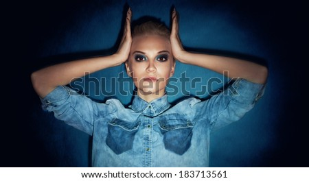 Portrait of beautiful blonde woman looking at camera. Girl with perfect makeup posing in studio. - stock photo