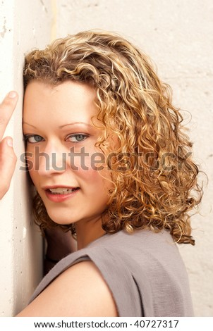 Portrait of beautiful blonde woman on concrete background - stock photo