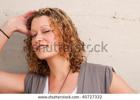 Portrait of beautiful blonde woman on concrete background