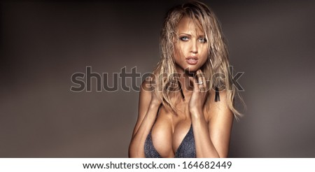 Portrait of beautiful blonde woman posing, looking at camera. - stock photo