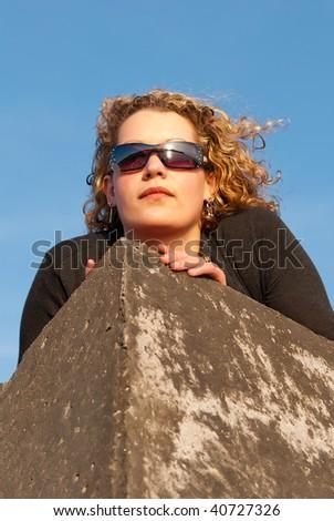 Portrait of beautiful blonde woman posing on rocks - stock photo
