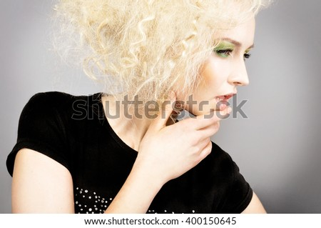 Portrait of beautiful blonde woman with creative hairstyle touching her chin or lips with a hand. Fashion photo - stock photo