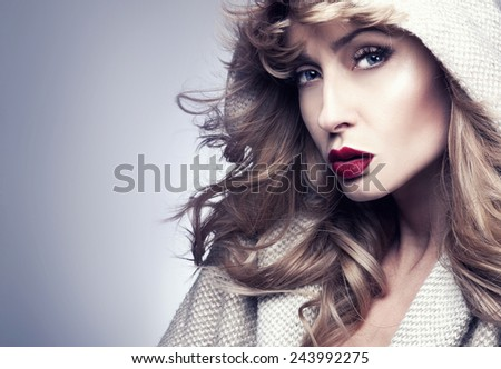 Portrait of beautiful blonde woman with long curly hair and perfect makeup. - stock photo