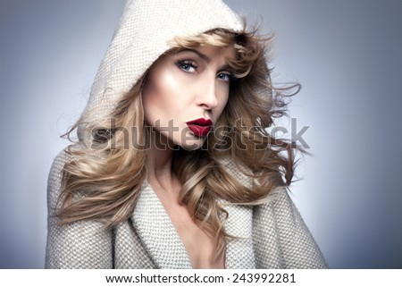 Portrait of beautiful blonde woman with long curly hair and perfect makeup. Girl looking at camera. - stock photo