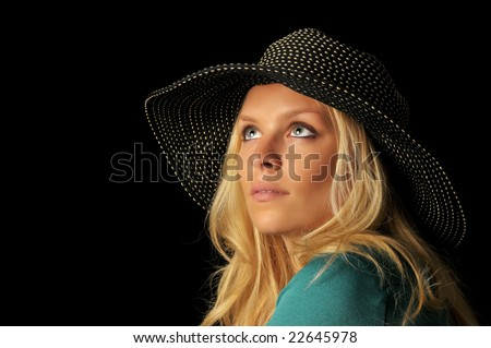 Portrait of beautiful blonde woman with spotted hat looking upward on black background.