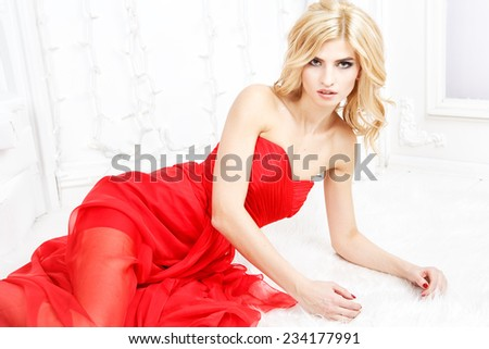 Portrait of beautiful blonde young woman in gorgeous red dress and evening make-up and hair style on a light background - stock photo
